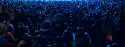 crowd of people at a concert in front of bright stage lights.
