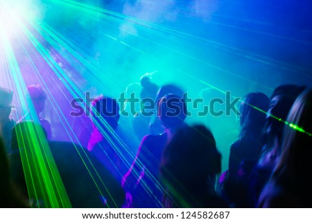 Crowd of people dancing under disco laser light.