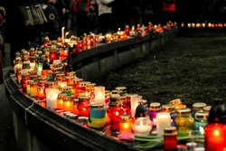 crowd of people lighting candles in city center, mourning victims in terrorism attacks and revolutions, sadness moment