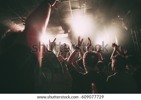Crowd of people on a rock concert with the hands raised up
