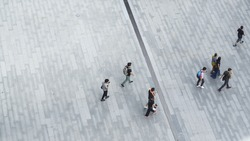 Crowd of people walk on open space concrete pavement from top view ,bird eye view