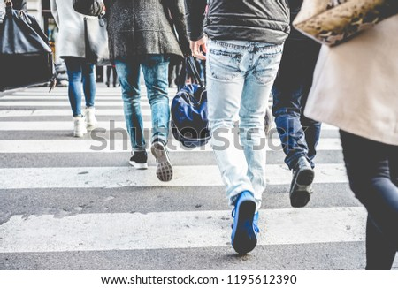 Crowd of people walking on zebra crossing street city center - Concept of modern, rushing, urban, city life, business, shopping - Soft focus on top guy left black shoe