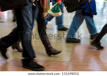 Crowd of people walking quickly in airport