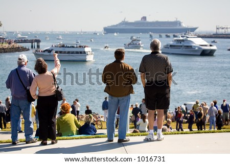 Crowd of people watching Queen Mary 2 meeting with Queen Mary in Long Beach, CA during the historic event.