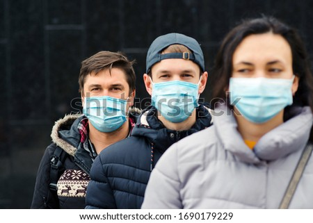 Crowd of people wearing medical masks. Coronavirus epidemic concept. Group of young volunteers outdoors. Coronavirus quarantine. Global pandemic. Worldwide coronavirus outbreak.