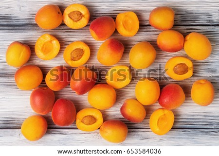 crowd of ripe apricots on white wooden background.