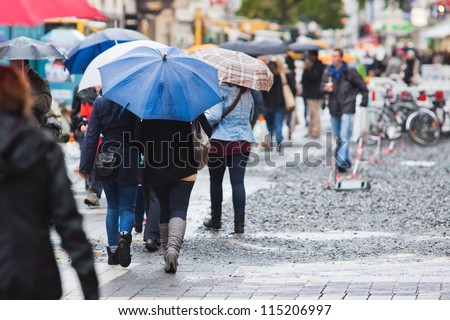crowd of shopping people with umbrellas on a rainy day in the city