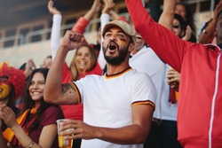 Crowd of spectators cheering at sports event, with a man holding a glass of beer. Germany football team supporters actively chanting in stadium.