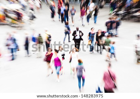 crowd of traveling people on a station courtyard with creative zoom effect