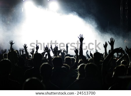 Crowd raising hands at a pop concert;  white and grey-blue fog