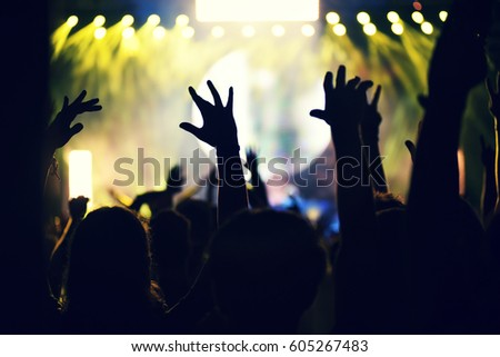 Crowd rocking during a concert with raised arms. Toned image #605267483