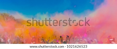 Crowd throwing bright colored powder paint in the air, Holi Festival Dahan