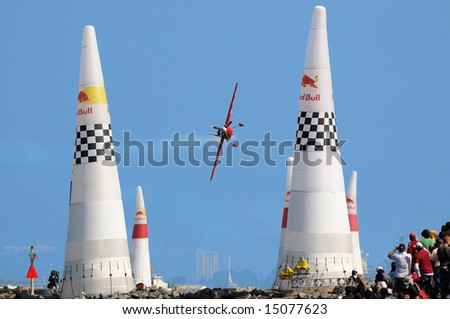 Crowd watches airplane going through obstacle course at Red Bull air race during San Francisco Fleet week - stock photo