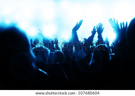 Crowd waving hands and sheering at the music concert