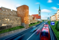 Crowded car road near fortess wall and St. Martin's church in Bratislava, Slovakia. Long exposure technic with motion cars and clouds