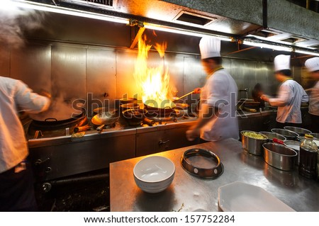 Crowded kitchen a narrow aisle working chef