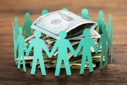 Crowdfunding Concept. Paper Cut Out Human Figures Around The Stack Of Hundred Dollar Bills