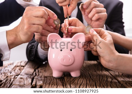 Crowdfunding Concept. People Inserting coins into piggybank