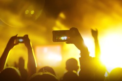 Crowds Enjoying Themselves At Music Festival, smartphone in hands during the rock concert, Raised hands