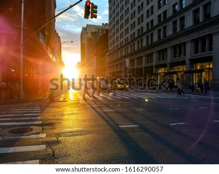 Crowds of busy people walking across the street in Midtown Manhattan with shining light of sunset in the background stock photo