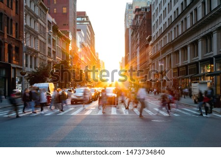 Crowds of busy people walking through the intersection of 5th Avenue and 23rd Street in Manhattan, New York City with bright sunset background