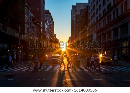 Crowds of diverse people walk across a busy intersection on 5th Avenue in Midtown Manhattan New York City with bright sunlight background stock photo