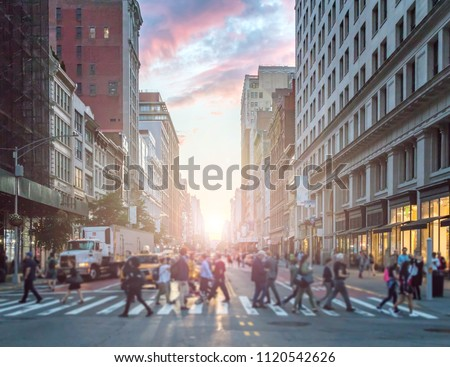 Crowds of people crossing an intersection in Manhattan, New York City with the colorful light of sunset in the background