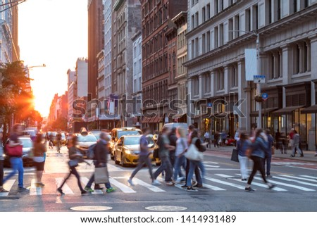 Crowds of people in motion across the busy intersection of 23rd Street and 5th Avenue in Midtown Manhattan, New York City NYC