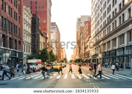 Crowds of people walking through a busy crosswalk at the intersection of 23rd Street and Fifth Avenue in Midtown Manhattan, New York City NYC