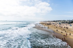 Crowds of tourists and sun bathers having fun and swimming at Huntington Beach.  California