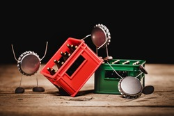Crown cork miniature figures carrying a red beer or beverage crate, hilarious conceptual scene for a warehouse or drinks
