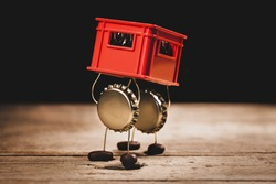 Crown cork miniature figures carrying a red beer or beverage crate, hilarious conceptual scene for drink promotion