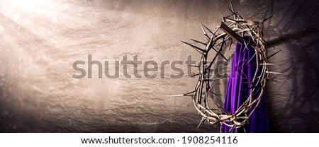 Crown Of Thorns And Purple Robe Hanging On Nail In Stone Wall With Light Rays  - Crucifixion Of Jesus Christ Stockfoto ©