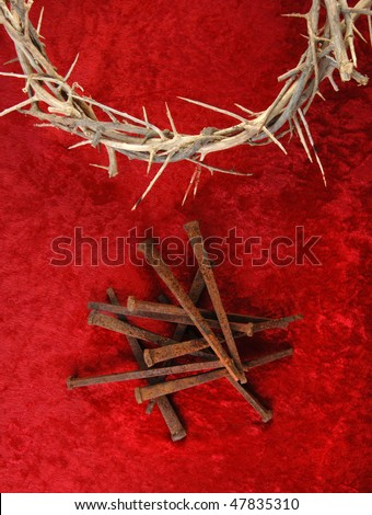 Crown of Thorns and rusty metal spikes on a rich red background.