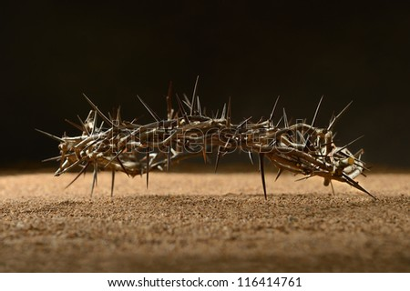 Crown of thorns laying on sand over dark background
