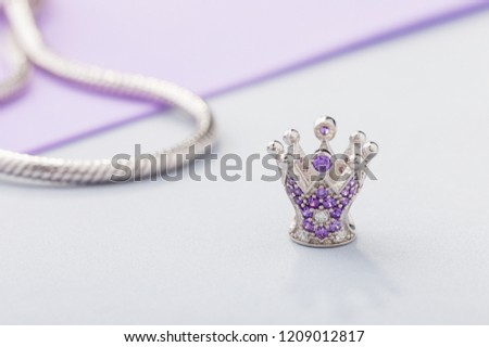 Crown shaped charm bead with purple gems for chain bracelet. Product concept for jeweler