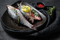 crucian carp with lemon and thyme on a black plate. River organic fish. Black background. Top view