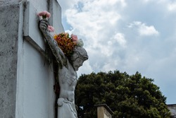 Crucified White JesusChrist Stone into a Cemetery adorned with multicolor flowers in hands, arms and flowers like a crown in head. Big tree and clouudy sky at background