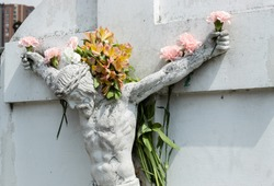 Crucified White JesusChrist Stone into a Cemetery adorned with multicolor flowers in hands, arms and flowers like a crown in head.