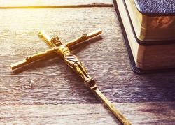 crucifix and books of holy bible  on  wooden background