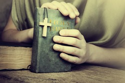 Crucifix in hand on the Holy Bible.