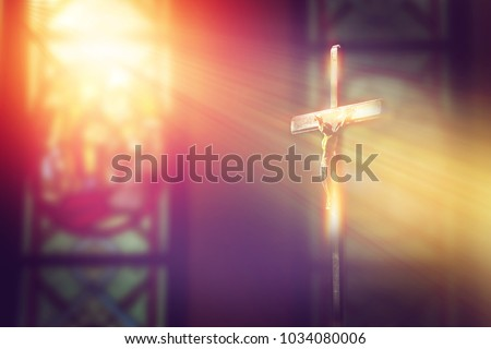 crucifix, jesus on the cross in church with ray of light from stained glass #1034080006