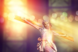 crucifix, jesus on the cross in church with ray of light from stained glass, easter festival of the Christian Church