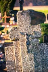 Crucifix on concrete cross in cemetery in autumn