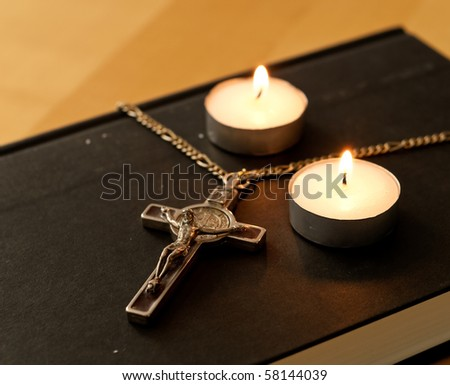 Crucifix with Lit Tea Candles on Bible