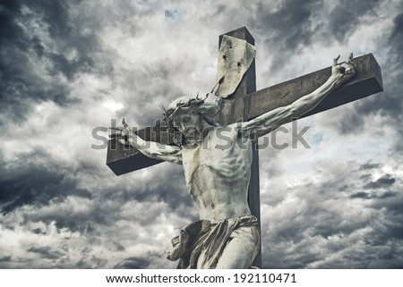 Crucifixion. Christian cross with Jesus Christ statue over stormy clouds. religion and spirituality concept.