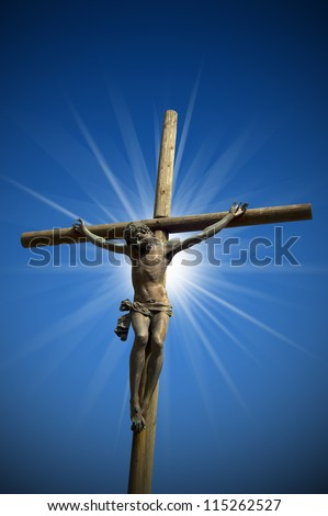 Crucifixion - The Jesus on the Cross / The cross (bronze and wood) - symbol of God's on blue sky