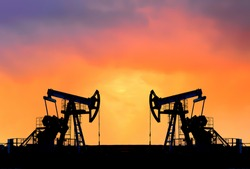 Crude oil pump jack at oilfield on atmospheric sunset backround. Fossil crude output and fuels oil production. Oil drill rig and drilling derrick. Global crude oil Prices, energy, petroleum demand