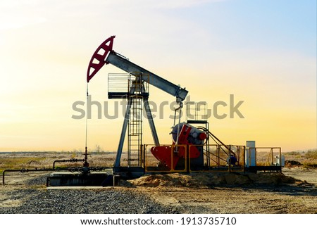 Crude oil pump jack at oilfield on sunset backround. Fossil crude output and fuels oil production. Oil drill rig and drilling derrick. Global crude oil Prices, energy, petroleum demand Stockfoto ©