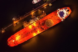 Crude oil shuttle tanker docked at night wtih light on creating an atmospheric glow with space for text.